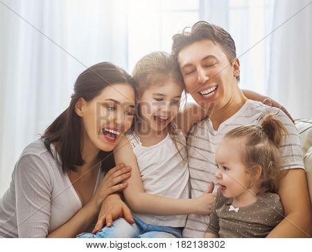 Happy father's day! Two children daughters with mother congratulate daddy. Mum, dad and girls laughing and hugging. Family holiday and togetherness.