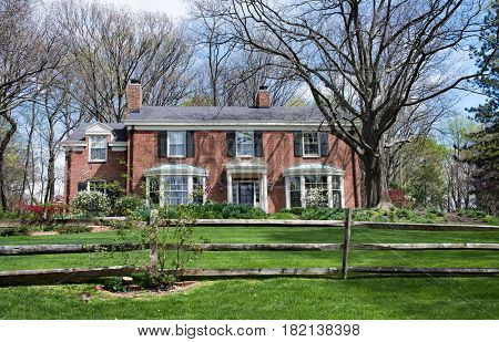Large Red Brick Country Home with Split Rail Fence