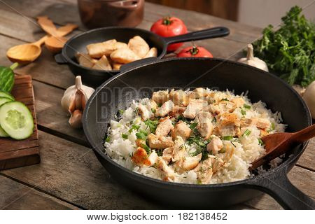 Frying pan with chicken and rice on kitchen table