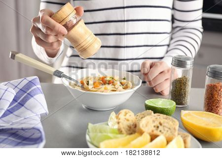 Woman eating chicken noodle soup at kitchen table
