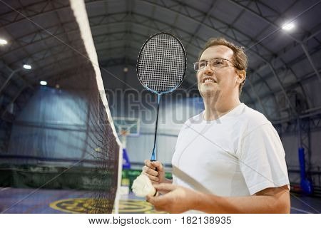 Smiling man in glasses with badminton racket and shuttlecock near net at sports ground.