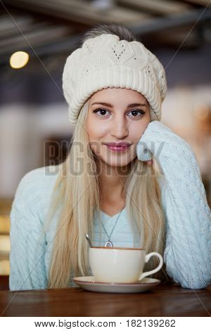 Young smiling blonde woman in knitted hat with fur pompom sits in cafeteria at table with cup of coffee.
