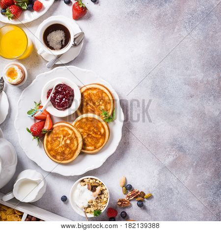 Healthy breakfast background with homemade pancakes and fresh berries, copy space, top view.