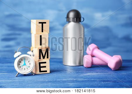 Cubes, alarm clock and bottle with dumbbells on color background. Time concept