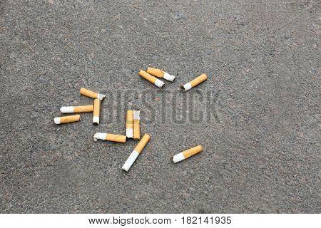 Cigarette butts on asphalt