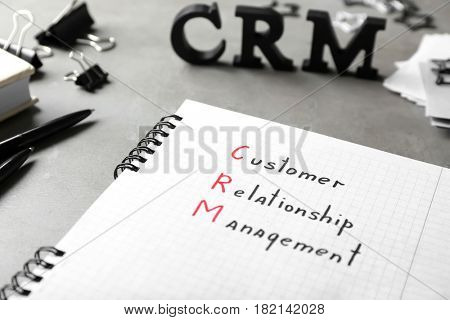 Notebook with written text CUSTOMER RELATIONSHIP MANAGEMENT on gray table