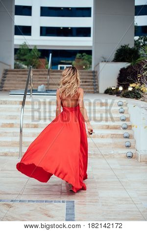 Girl with long curly hair in long red dress goes to the steps.Girl in red dress. Long red dress flutters in the wind