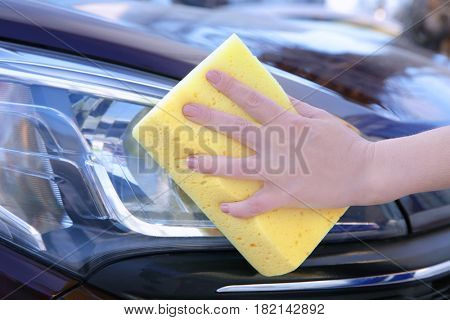 Female hand with sponge cleaning car headlight