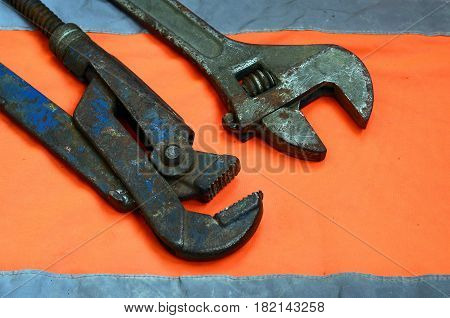 Adjustable And Pipe Wrenches Against The Background Of An Orange Signal Worker Shirt