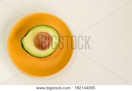 Avocado fruit green half with seed on the yellow plate isolated white background