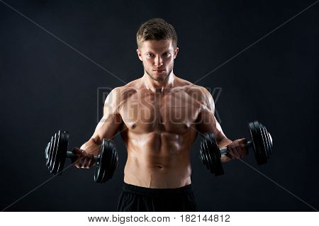 Handsome young fierce muscular male athlete with stunning sexy body and perfect abs looking confidently to the camera lifting heavy weights on black background motivation determination effort.