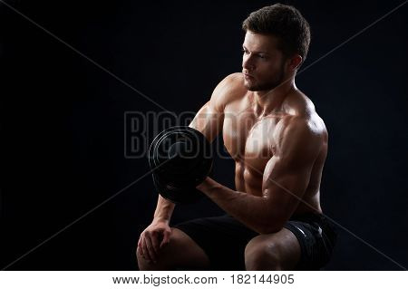 Handsome young sportive shirtless man with muscular strong sexy body doing exercises using dumbbell against black background copyspace gym athletics physique sports motivation achievement gaining.