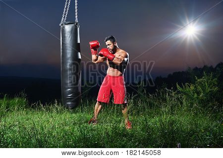 Full length shot of a muscular powerful boxer training shirtless outdoors at night working out with a punching bag copyspace nature concentration motivation sport athlete sportsman fighter combat.