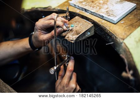 Jeweler using saw to create new jewelry
