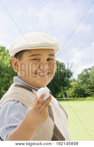 Hispanic boy playing golf