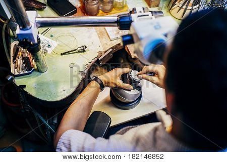 Professional jeweler working on a pieces of metal using an optical device