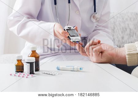 the doctor measuring blood sugar on background table