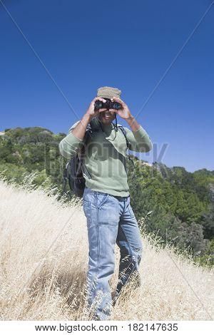 Mixed race man backpacking on hillside with binoculars