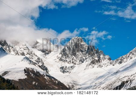 Snow covered mountains and their peaks in the clouds against the blue sky in Georgia. Greater Caucasus Mountains