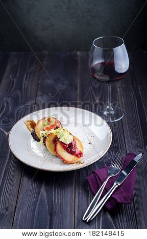 Goose liver with cherry sauce and apples and a glass of wine