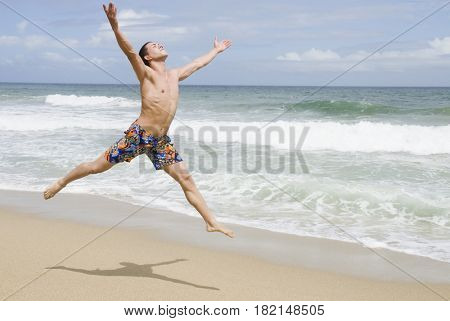Hispanic man at beach jumping in mid-air