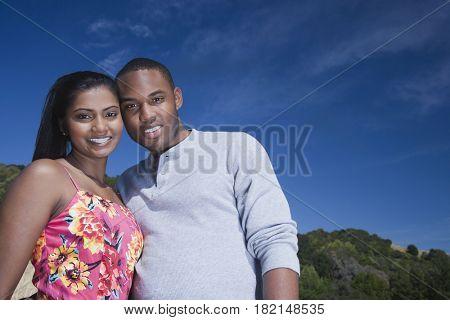 Multi-ethnic couple hugging in rural area