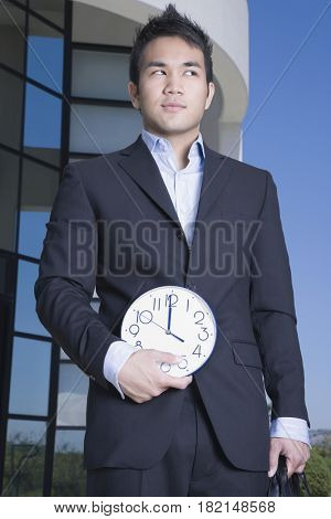 Asian businessman holding clock outdoors