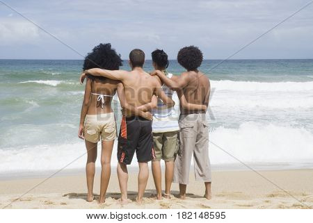 Multi-ethnic friends hugging at beach