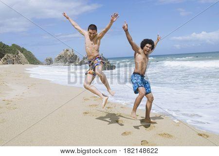 Friends at beach jumping in mid-air