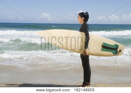 Hispanic woman at beach with surfboard