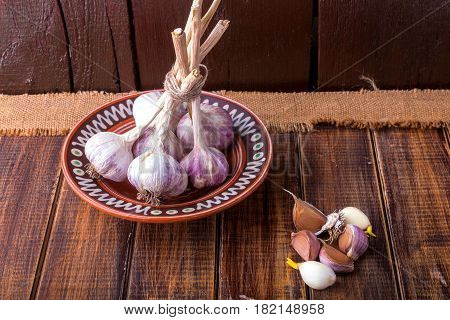 Garlic In Brown Plate Wrapped With Twine On Wooden Background. Rustic.