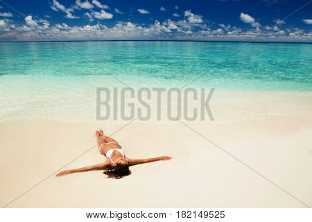 Cute woman relaxing on the summer beach. Happy lifestyle. White sand, blue sky and crystal sea of tropical beach. Vacation at Paradise. Ocean beach relax, travel to islands