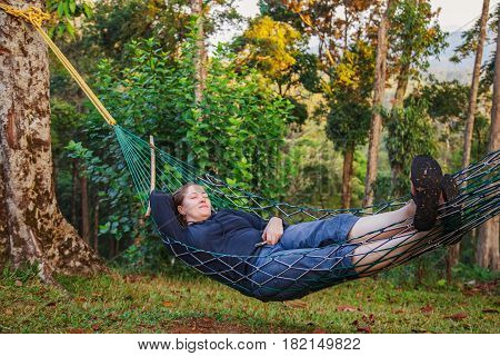 Woman resting in a hammock after trekking in the jungle. The concept of active life.