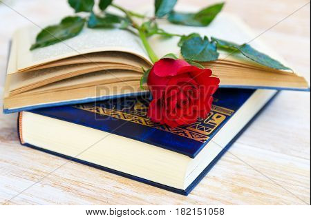 Red rose and open old book on wooden background. Concept for Sant Jordi the Saint Georges Day celebrated on 23rd of April.Also this is World Book Day.