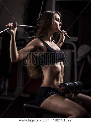 Young business woman doing exercise on a fitness machine in a fitness club. Photo on a dark background.