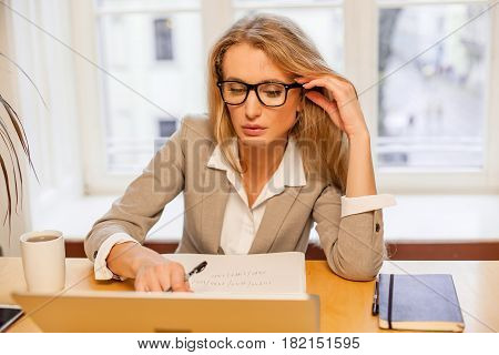 Atrractive young blonde-haired wonman wearing glasses and working with laptop. Woman sitting in a nice cozy office.