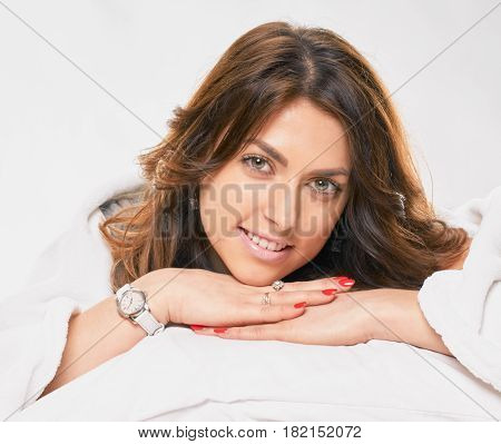 Portrait of pretty smiling woman lying in bed at morning