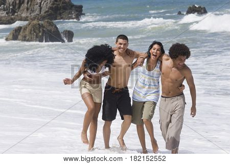 Multi-ethnic friends walking on beach