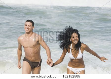 Multi-ethnic couple holding hands at beach