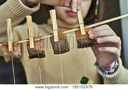 Girl hanging used tea bags as washed clothes for drying on the clothesline with clothes pegs