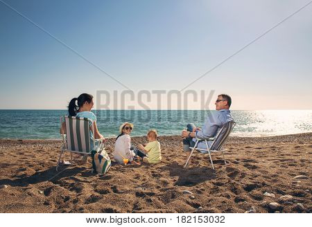 Portrait of a happy family in summer nature. Mother and father are sitting on a beach deck chair daughter and son playing