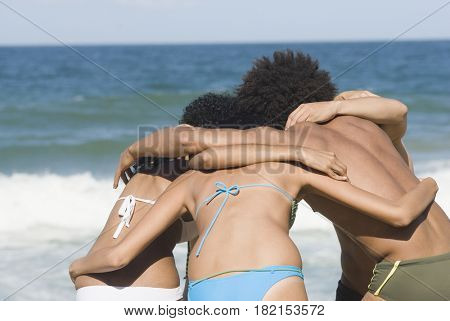 Multi-ethnic friends hugging on beach