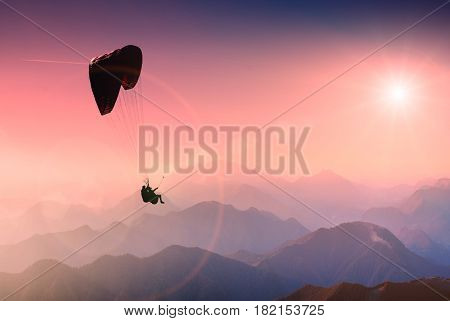 Paraglide silhouette in a sky over the mountain peaks.