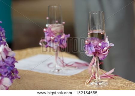 Wedding champagne flutes decorated with pearls and violet flowers