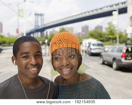 African brother and sister sharing earbuds from mp3 player