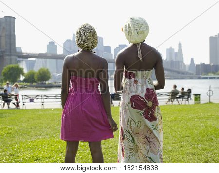 African woman standing at urban waterfront with friend