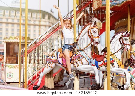 Girl riding on a merry go round. Little girl playing on carousel, summer fun, happy childhood and vacation concept.