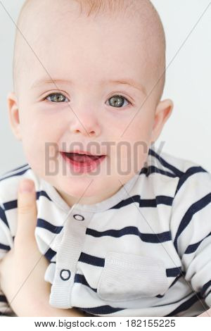 Vertical studio portrait of adorable little boy looking at camera.