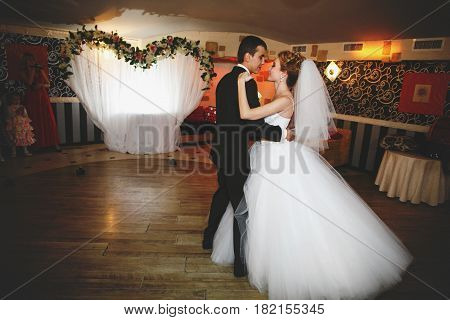 Groom Holds Bride With His Strong Hands During Their First Dance