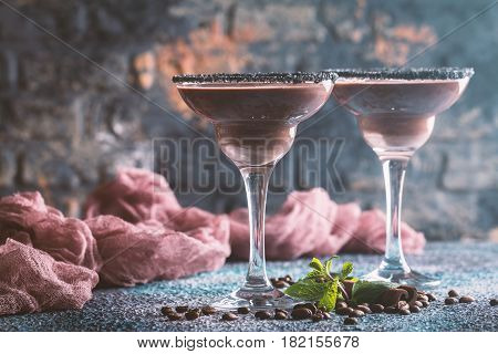 glasses of cream coffee cocktail or chocolate martini on blue background